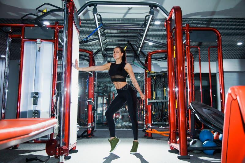 Le jeune athlète féminin avec le corps parfait d'ajustement pose au gymnase moderne photographie stock