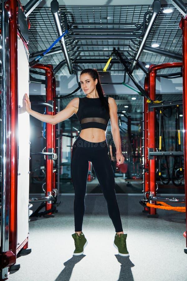 Le jeune athlète féminin avec le corps parfait d'ajustement pose au gymnase moderne images stock