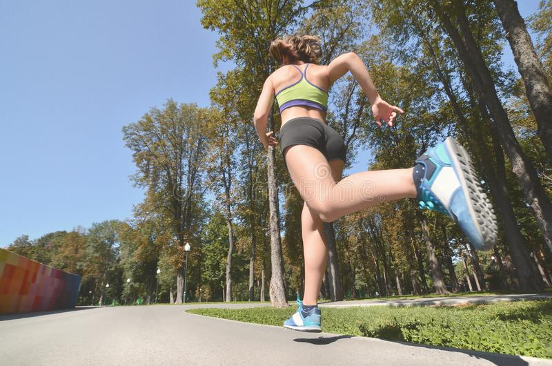 Le jeune athlète féminin caucasien dans un soutien-gorge vert clair de sports et des shorts de sports court en parc d'été en plei photo libre de droits