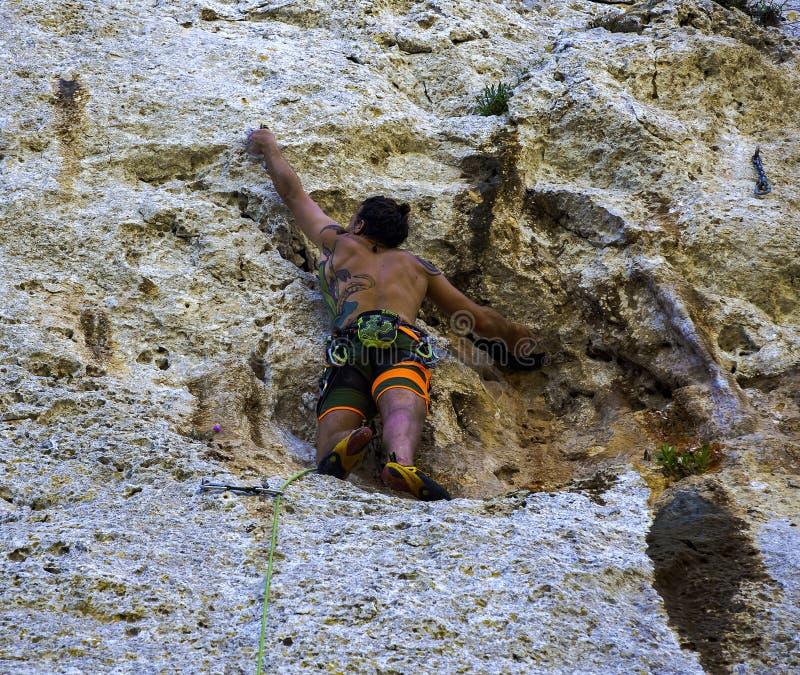 Le jeune athlète s'élève sur une roche rocheuse photo libre de droits