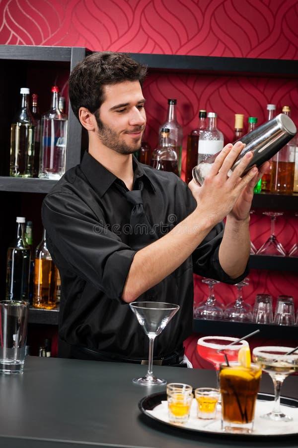 Le jeune barman effectuent le cocktail secouant des boissons images stock