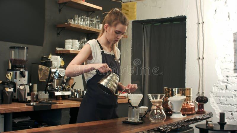 Le jeune barman femelle dans le café moderne à la mode de café verse l'eau bouillante au-dessus des marcs de café faisant un vers photos libres de droits