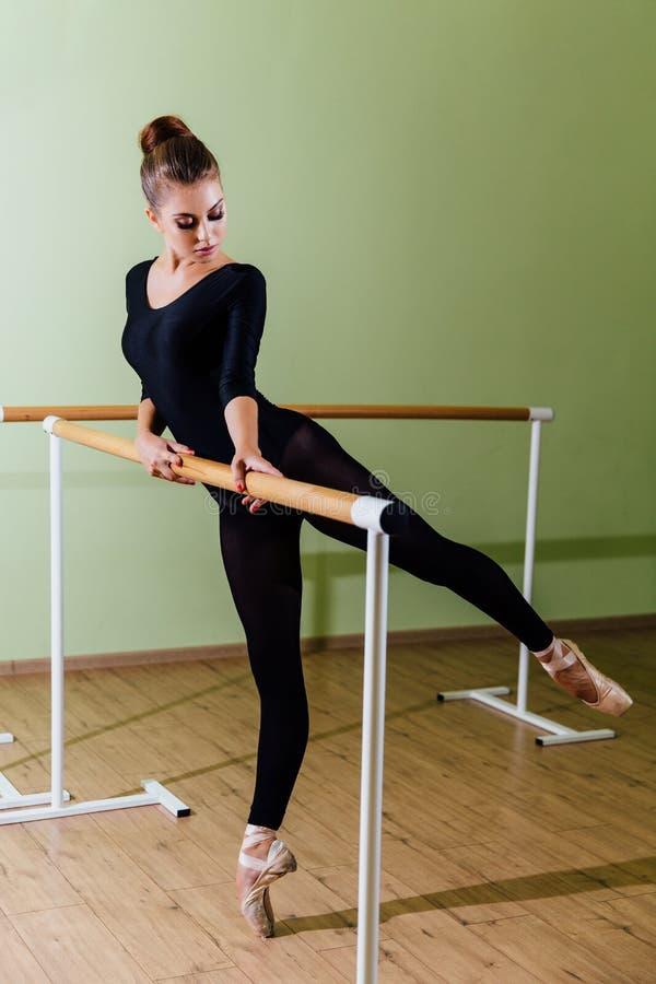 Le jeune beau danseur posant dans le ballet d'esprit de studio barrent sur la pointe des pieds Brune sexy moderne images stock