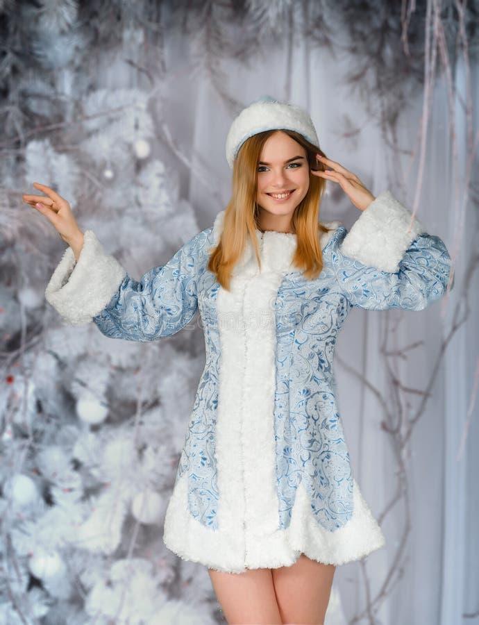 Le jeune beau portrait de sourire de fille dans la forêt neigeuse d'hiver, neigent jeune fille photo stock