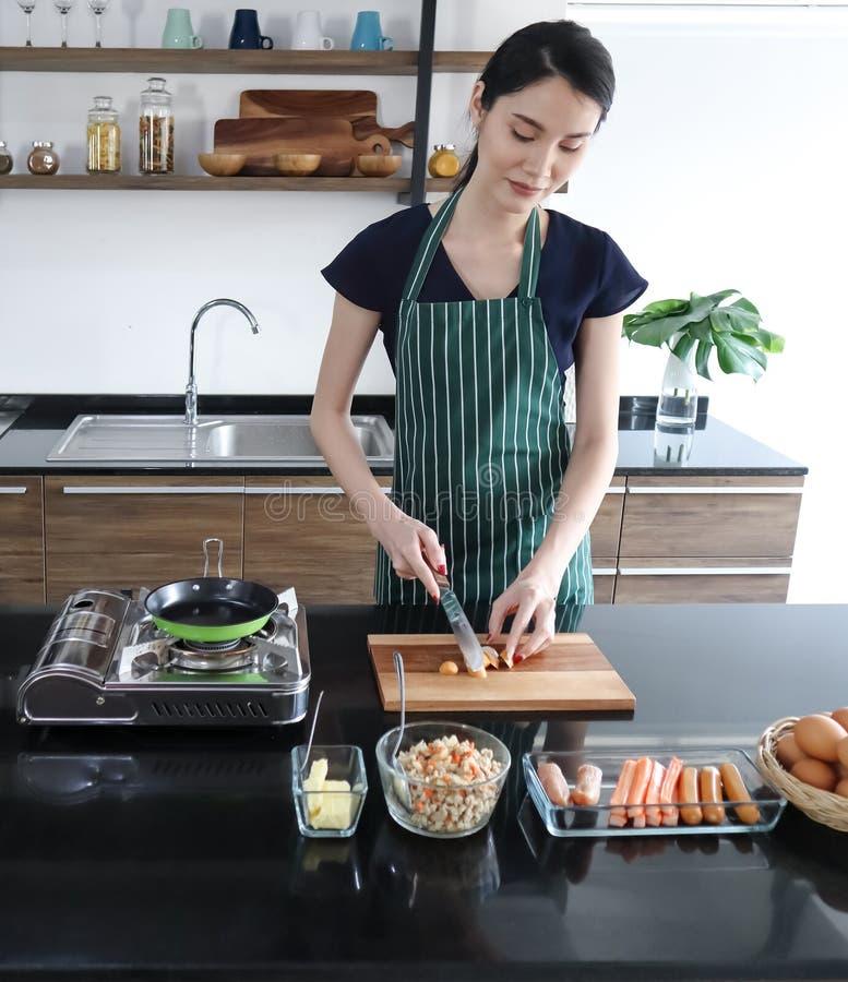 Le jeune beau sourire asiatique de woth de femme coupe en tranches la saucisse du plat en bois images libres de droits