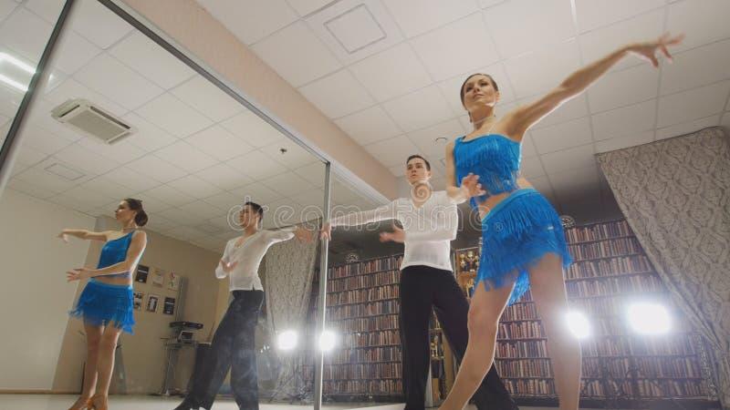 Le jeune beaux homme et la femme dansant et préparant la danse latine dans des costumes dans le studio, se ferment, dans l'action images stock
