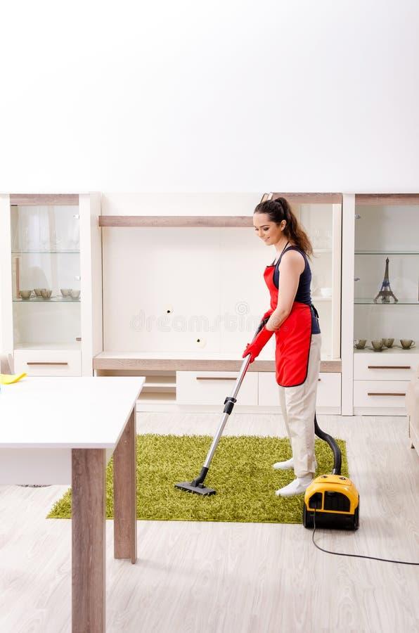 Le jeune bel appartement de nettoyage de femme photo stock