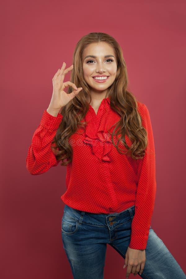 Le jeune bel ok heureux d'apparence de femme se connectent le fond rose coloré Fille d'étudiant avec le geste correct, émotions p photo stock