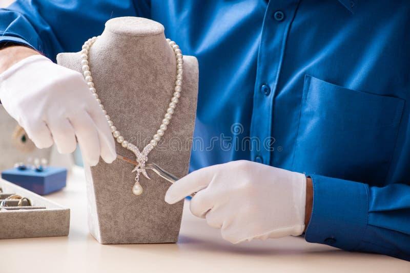 Le jeune bijoutier travaillant dans son atelier image stock