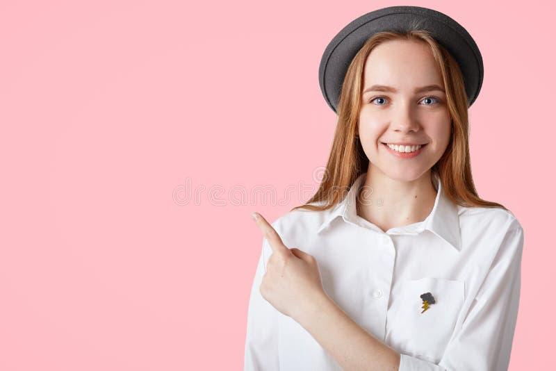 Le jeune bleu assez avec plaisir a observé la femelle avec de longs cheveux, yeux bleus, utilise le chapeau noir élégant et la ch photo stock