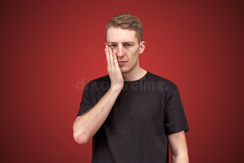 Le jeune camarade masculin attirant tient la paume à la joue avec une expression perturbée, ou un mal de dents harcelant images stock
