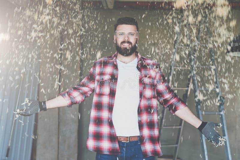 Le jeune charpentier barbu heureux de hippie d'homme en verres de construction se tient dans l'atelier De la sciure ci-dessus de  image stock