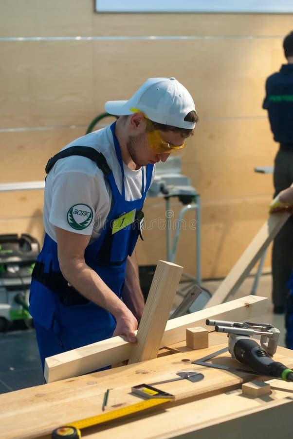 Le jeune charpentier effectue la tâche de la concurrence images libres de droits