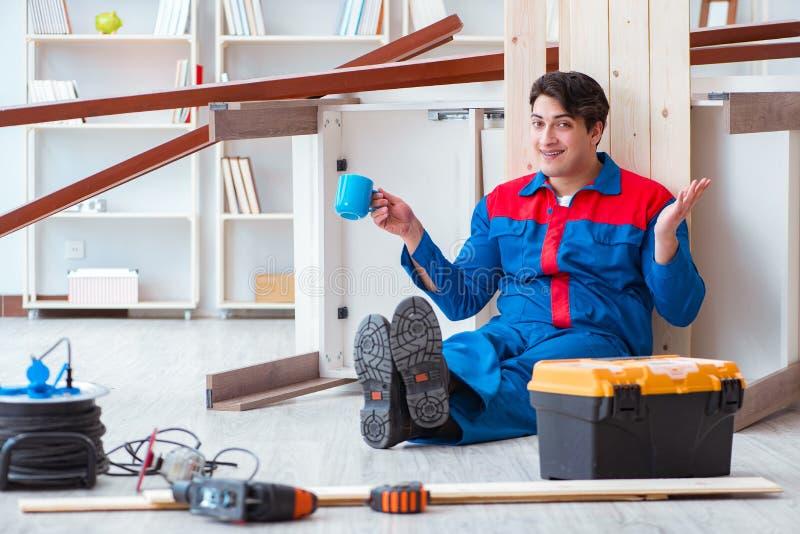 Le jeune charpentier faisant la pause du travail avec les planches en bois image stock