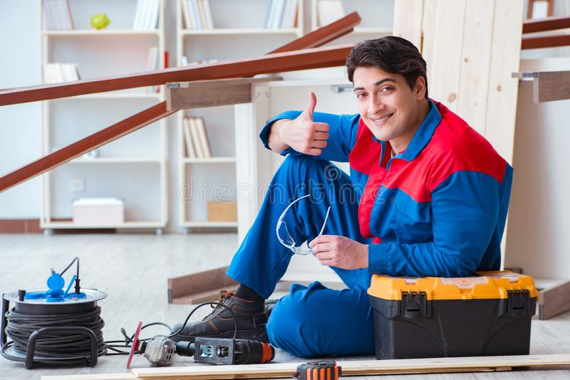 Le jeune charpentier faisant la pause du travail avec les planches en bois photo libre de droits