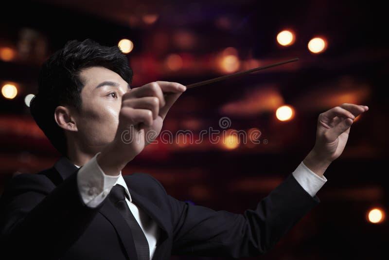 Le jeune chef d'orchestre avec le bâton a augmenté à une interprétation images libres de droits