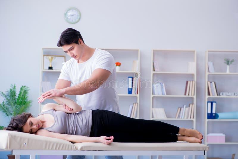 Le jeune chiroprakteur de docteur massant la femme patiente féminine photographie stock