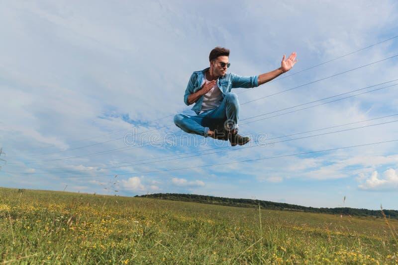 Le jeune combattant avec des lunettes de soleil saute dehors sur le champ photos stock