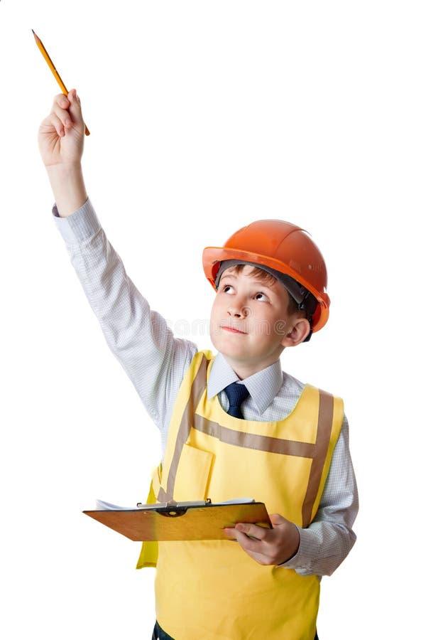 Le jeune constructeur dans le gilet et le casque révèle images libres de droits