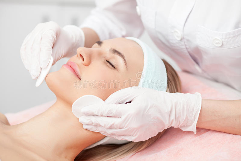 Le jeune cosmetologist professionnel guérit la femelle photo stock