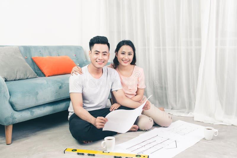 Le jeune couple adulte asiatique attrayant regardant la maison prévoit photo libre de droits