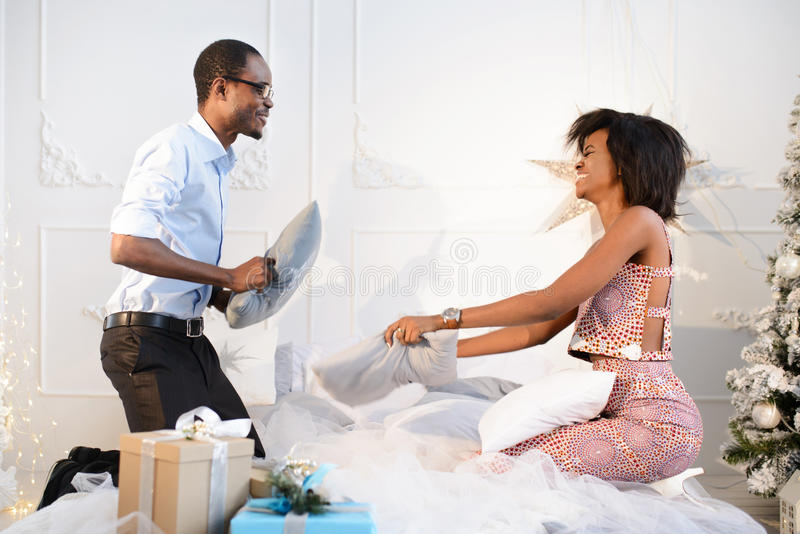 Le jeune couple afro-américain heureux affectueux combat avec des oreillers comme de petits enfants le réveillon de Noël près du images stock