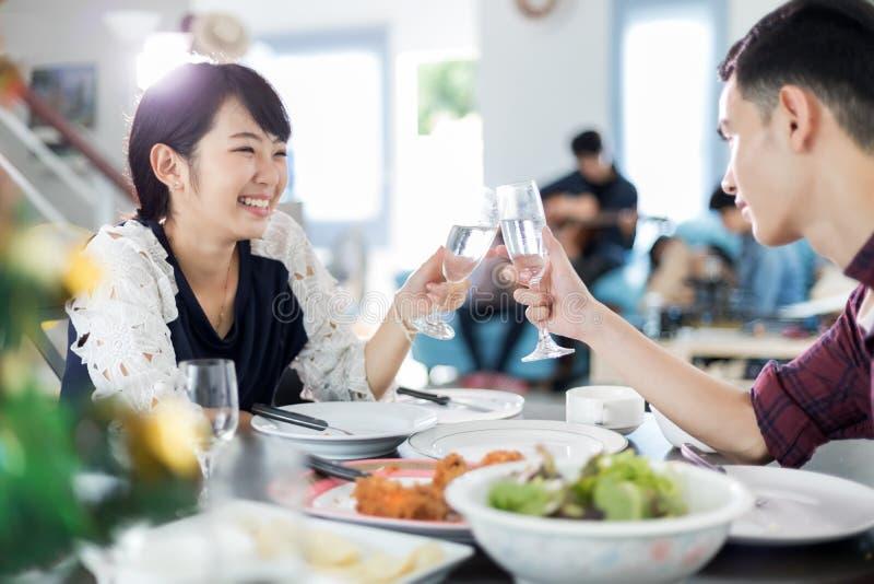 Le jeune couple asiatique appréciant une soirée romantique de dîner boit le wh photos stock