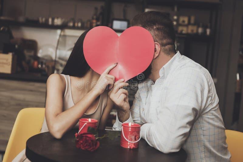 Le jeune couple avec du charme se cache derrière le coeur de papier images libres de droits