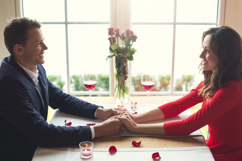 Le jeune couple dînant romantique dans se tenir se reposant de restaurant remet le regard sur l'un l'autre photo stock