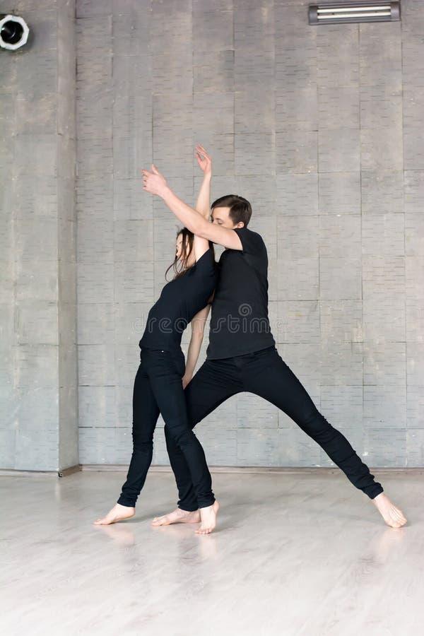 Le jeune couple dans le noir danse photos libres de droits