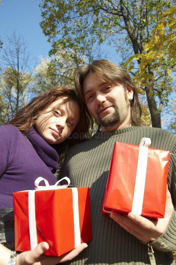 Le jeune couple donne des cadeaux photographie stock libre de droits