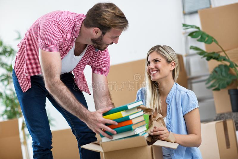 Le jeune couple emballe des livres dans les boîtes photo libre de droits