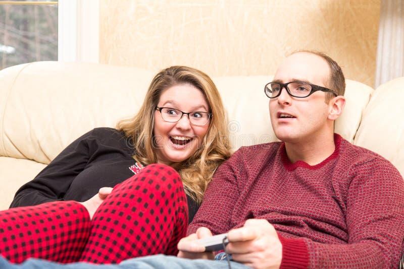 Le jeune couple enthousiaste joue le jeu vidéo photos libres de droits