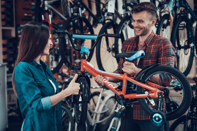 Le jeune couple heureux choisit des enfants va à vélo dans le magasin photo libre de droits