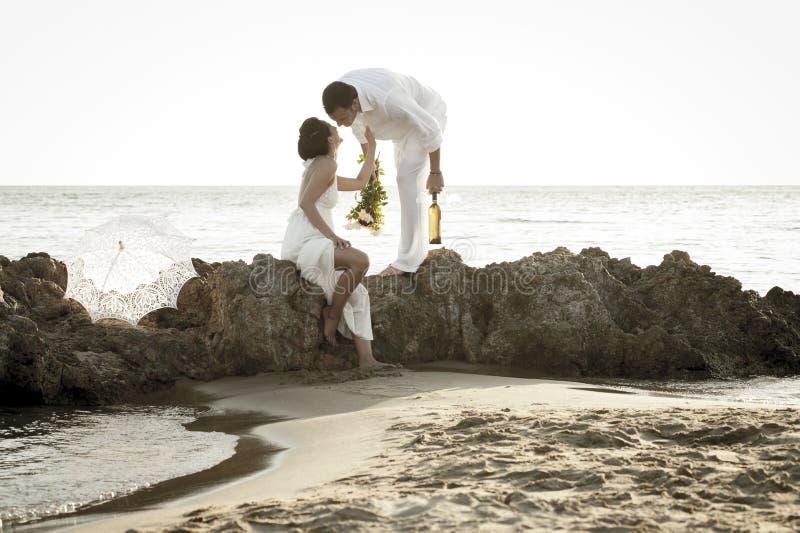 Le jeune couple heureux détendant ensemble sur la plage bascule au lever de soleil images libres de droits