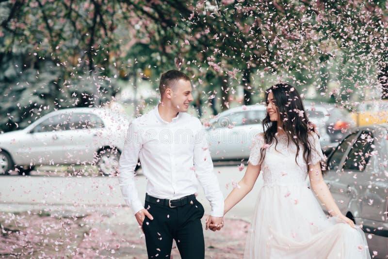 Le jeune couple heureux dans l'amour apprécie la journée de printemps, homme affectueux se tenant dessus remet à sa femme la marc image stock