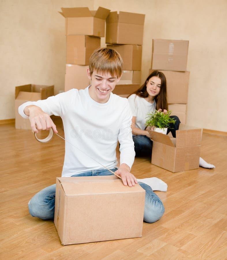 Le jeune couple heureux emballe des boîtes en carton pour entrer dans une nouvelle maison photos libres de droits