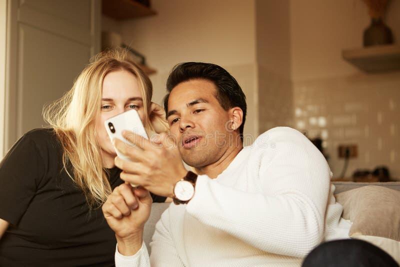 Le jeune couple heureux fait le selfie, regardant la caméra photo stock