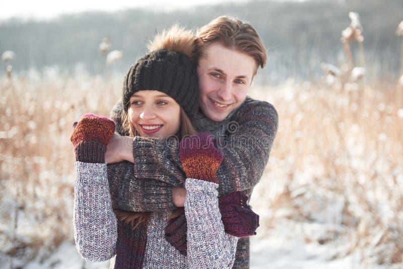 Le jeune couple heureux a l'amusement sur la neige fraîche au jour ensoleillé de bel hiver des vacances images libres de droits
