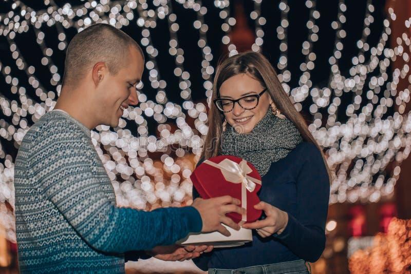 Le jeune couple heureux ouvre ensemble la boîte avec un cadeau image stock