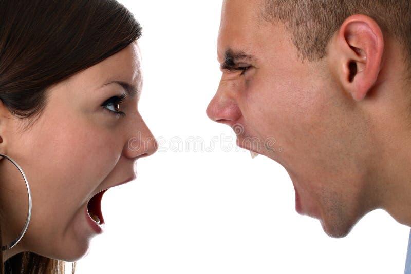 Le jeune couple hurle à l'un l'autre a isolé sur le blanc photo stock