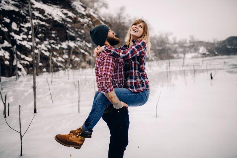 Le jeune couple a l'amusement pendant la promenade d'hiver sur la glace du lac congelé photos stock