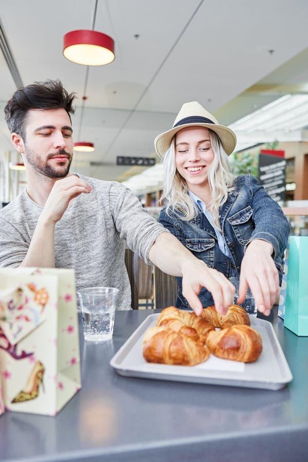 Le jeune couple mange des croissants dans les Bistros image stock