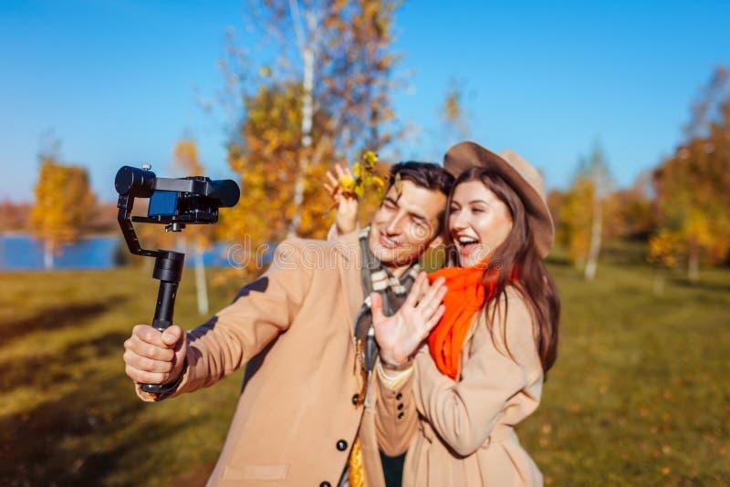 Le jeune couple marche dans l'homme de forêt d'automne et la longueur de pelliculage de bloggers de femme Les gens ayant l'amusem photo libre de droits