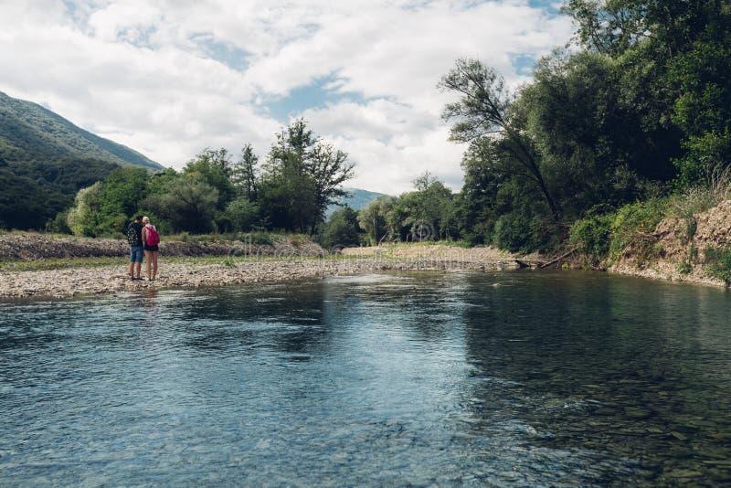 Le jeune couple marche le long de l'été de rivière, ensemble vue arrière de concept photographie stock