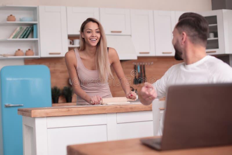 Le jeune couple marié communique dans leur cuisine photographie stock libre de droits