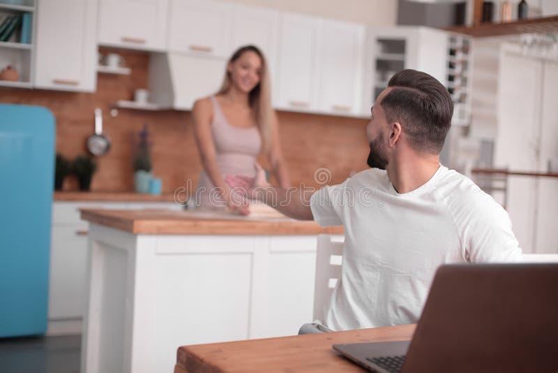 Le jeune couple marié communique dans leur cuisine images stock