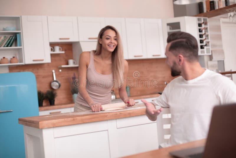 Le jeune couple marié communique dans leur cuisine photographie stock