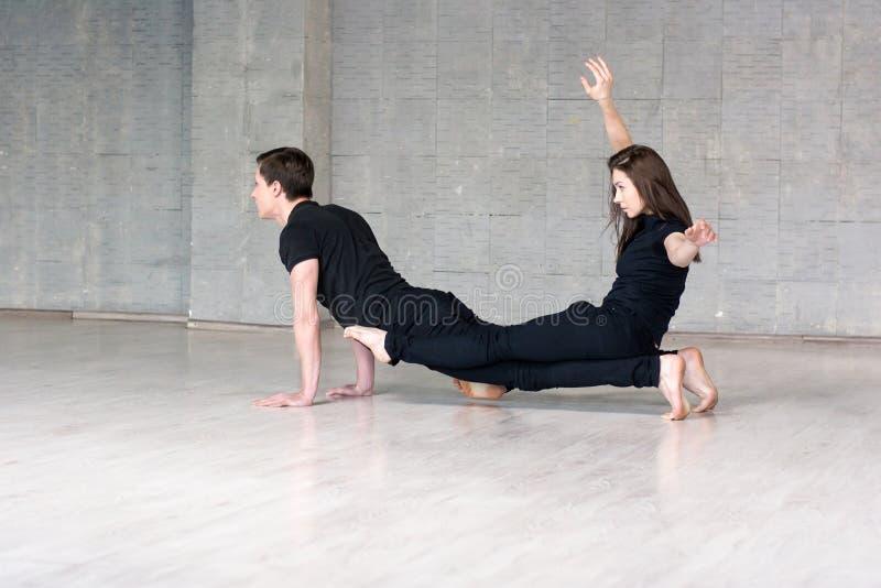 Le jeune couple pratique l'équilibre acrobatique photographie stock