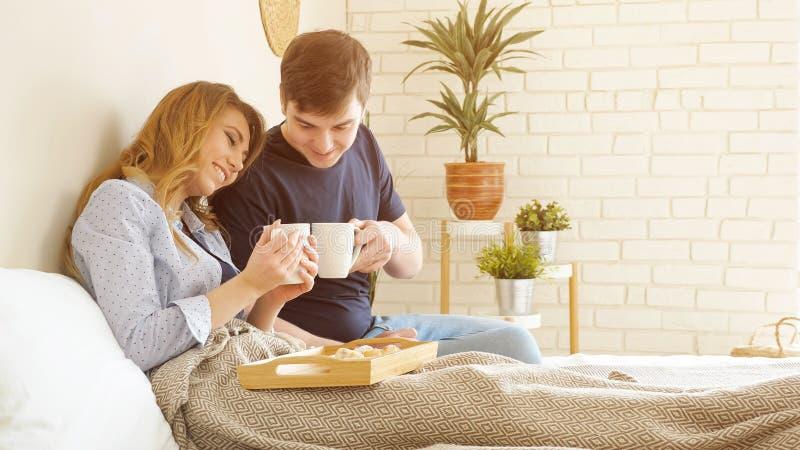 Le jeune couple prend le petit déjeuner en café savoureux de boissons de lit miling dans la chambre à coucher images libres de droits